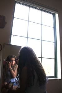 Dahlia Dandashi swipes a few strokes of mascara in her dorm room mirror.