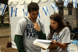 Student Michael herschmann, left, and Co-Director of Israel Block Party, Rebecca Hanai, right, discus preparations prior to the opening of the Israel Block Party.